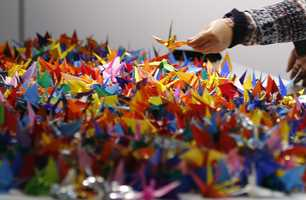A Japanese visitor offers a paper crane folded by her to pay her respects to the late U.S. President John F. Kennedy at a memorial venue specially set up for his Japanese fans in Tokyo Friday, Nov. 22, 2013 to mark the 50th anniversary of his assassination. Japanese JFK fans took photos with his portrait, folded paper cranes and watched his inaugural ceremony on a monitor Friday to express admiration on the anniversary.