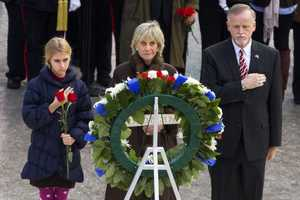 An unidentified girl, left, holds a rose during a wreath laying ceremony with former Ambassador to Ireland Jean Kennedy Smith, center, and Patrick Hallinan, executive director of Army National Military Cemeteries, at the grave of John F. Kennedy at Arlington National Cemetery, in Arlington, Va., Friday, Nov. 22, 2013, on the 50th anniversary of Kennedy's death.
