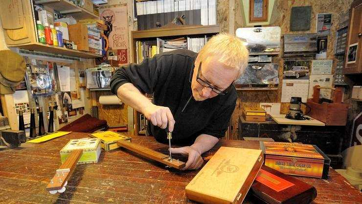 Steve Butler makes some adjustments on a cigar-box guitar in his garage, where he films a local cable television show that has aired in 45 states and Canada.