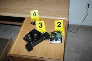 Placard #2 shows an empty ear plug package, #3 shows a damaged hard drive and #4 shows keys to a gun safe and filing cabinet in a computer room.