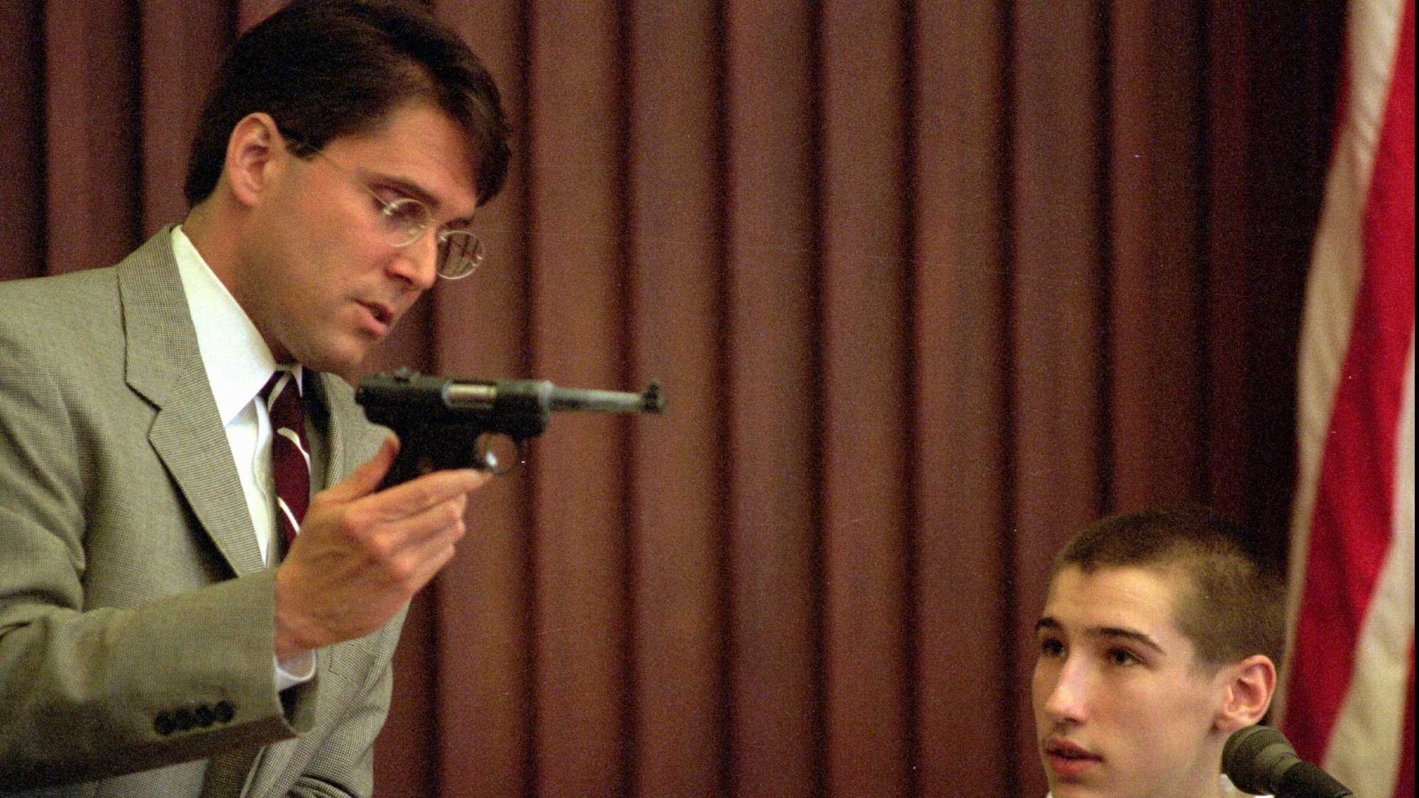 In his second day of testimony at Strafford County Superior Court, in Dover, N.H., Wednesday, May 14, 1997, Jeffrey Dingman, 15, looks on as New Hampshire assistant attorney general John Kacavas shows the .22 caliber pistol that was used to kill Jeffrey's parents, Vance and Eve Dingman. Jeffrey is testifying against his older brother, Robert, 18, who is being tried on two counts of first degree murder.