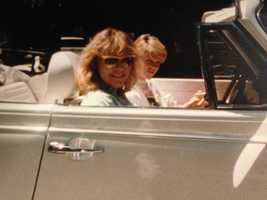 Heather Unruh sitting in her first car, a VW bug, with her sister.
