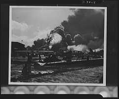 Pearl Harbor bombing. Naval air station. This is the wreckage-strewn naval air station at Pearl Harbor following one of the Japanese sneak attacks on the morning of December 7, 1941. In the background, an explosion sends a mass of flames and smoke high in the sky