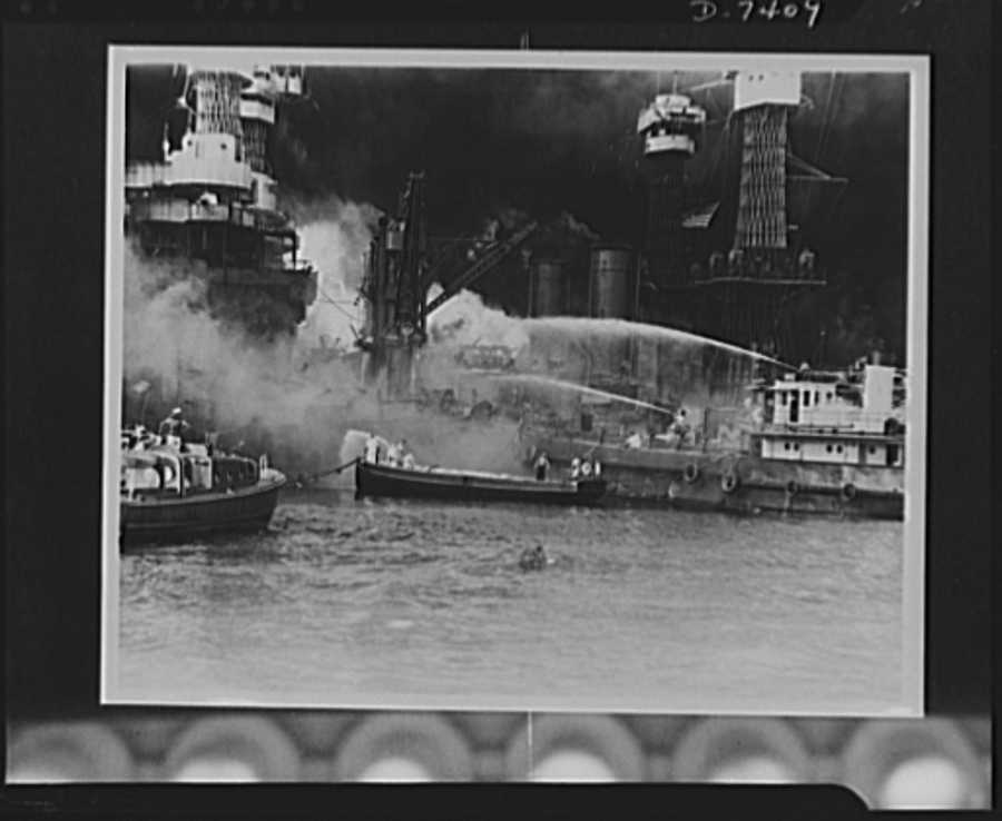 Pearl Harbor bombing. USS West Virginia a flame. Disregarding the dangerous possibilities of explosions, U.S. sailors man their boats at the side of the burning battleship, USS West Virginia, to better fight the flames started by Japanese torpedoes and bombs. Note the national colors flying against the smoke-blackened sky