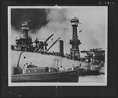 Pearl Harbor bombing. USS Oklahoma. Rescue crews are shown here working on the upturned hull of the 29,000 ton battleship USS Oklahoma, which capsized in Pearl Harbor after being blasted by Japanese warplanes. Holes were burned through the hull to permit the rescue of some of the men trapped below. Note one of the Oklahoma's launches in the foreground. The battleship, USS Maryland is in the background