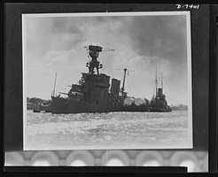 Pearl Harbor bombing. USS Raleigh. Torpedoed and bombed, the 7,050 ton light crusier USS Raleigh is held afloat near her anchorage in Pearl Harbor by a barge. The capsized USS Utah is in the background. The Raleigh rejoined the fleet months ago