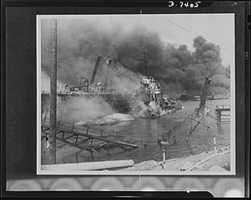 Pearl Harbor bombing. USS Shaw. Hit by three bombs which exploded her forward magazine, the 1,500 ton destroyer Shaw lies a twisted mass of wreckage in the heavily-bombed floating drydock YFD-2. Note the bow of the Shaw lying on its side in the foreground. Part of the drydock, at right, is under water while the other side is listing heavily. Both the Shaw and the drydock are now back in use