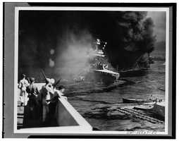 California hit. Battered by aerial bombs and torpedoes, the U.S.S. California settles slowly into the mud and muck of Pearl Harbor. Clouds of black oily smoke pouring up from the California and her stricken sister ships conceal all but the hulk of the capsized U.S.S. Oklahoma at extreme right