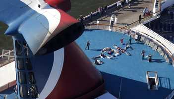 "Passengers spell out the word ""HELP"" aboard the disabled Carnival Lines cruise ship Triumph as it is towed to harbor off Mobile Bay, Ala., Thursday, Feb. 14. The ship with more than 4,200 passengers and crew members had been idled for nearly a week in the Gulf of Mexico following an engine room fire."