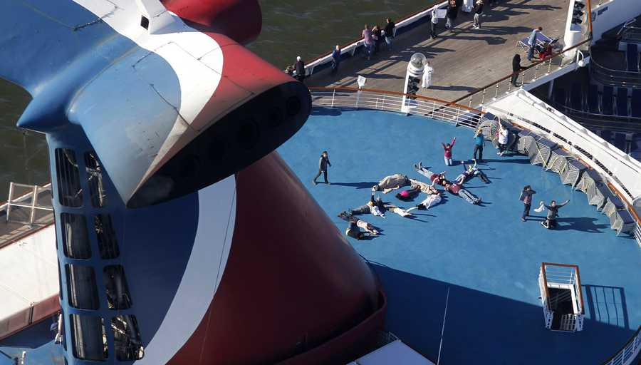 """Passengers spell out the word """"HELP"""" aboard the disabled Carnival Lines cruise ship Triumph as it is towed to harbor off Mobile Bay, Ala., Thursday, Feb. 14. The ship with more than 4,200 passengers and crew members had been idled for nearly a week in the Gulf of Mexico following an engine room fire."""