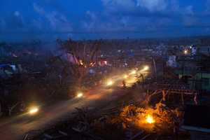 Typhoon Haiyan survivors ride motorbikes through the ruins of the destroyed town of Guiuan, Philippines on Thursday, Nov. 14. Typhoon Haiyan destroyed tens of thousands of buildings and displacing at least a half-million people.
