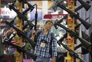 Michael Kiefer, of DeFuniak Springs, Fla., checks out a display of rifles at the Rock River Arms booth during the 35th annual SHOT Show, Thursday, Jan. 17, 2013, in Las Vegas -- one month after the deadly Newtown school shooting.
