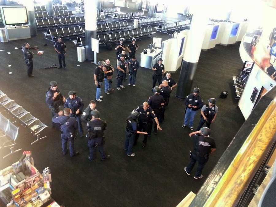 Police officers stand near an unidentified weapon in Terminal 3 of the Los Angeles International Airport on Friday, Nov. 1, 2013. Officials said a gunman who opened fire in the terminal was wounded in a shootout with police and taken into custody.