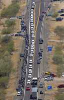 A procession of 19 hearses for the 19 fallen Arizona firefighters drives through the desert, Sunday, July 7 near Wickenburg, Ariz, The elite crew of firefighters were overtaken by the out-of-control blaze as they tried to protect themselves from the flames under fire-resistant shields.
