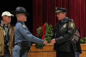 A member of the Maine State Police presents a wreath to Topsfield Police Chief Evan E.J. Haglund as Morrill Worcester looks on.
