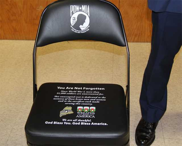 A chair to remember those missing in action is guarded by a member of the Maine State Police.