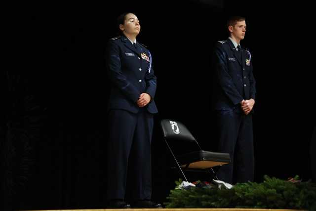 Cadets in the Maine Civil Air Patrol stand near the POW/MIA chair as it rests on stage.