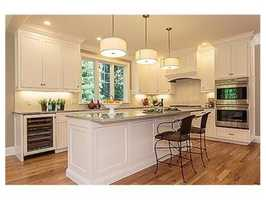 The home offers quartzite Kitchen with floor-to-ceiling linen white cabinetry.