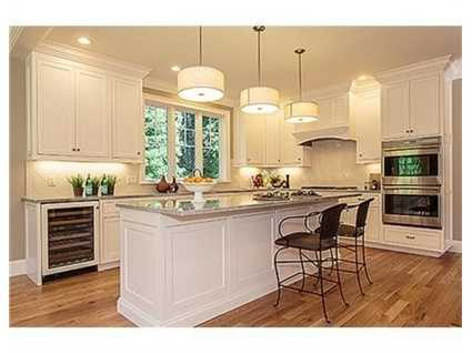 Thehome offers quartzite Kitchen with floor-to-ceiling linen white cabinetry.