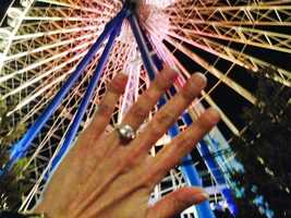 Kristina D'Agostino holds her engagement ring in front of the carousel in Lyon, France