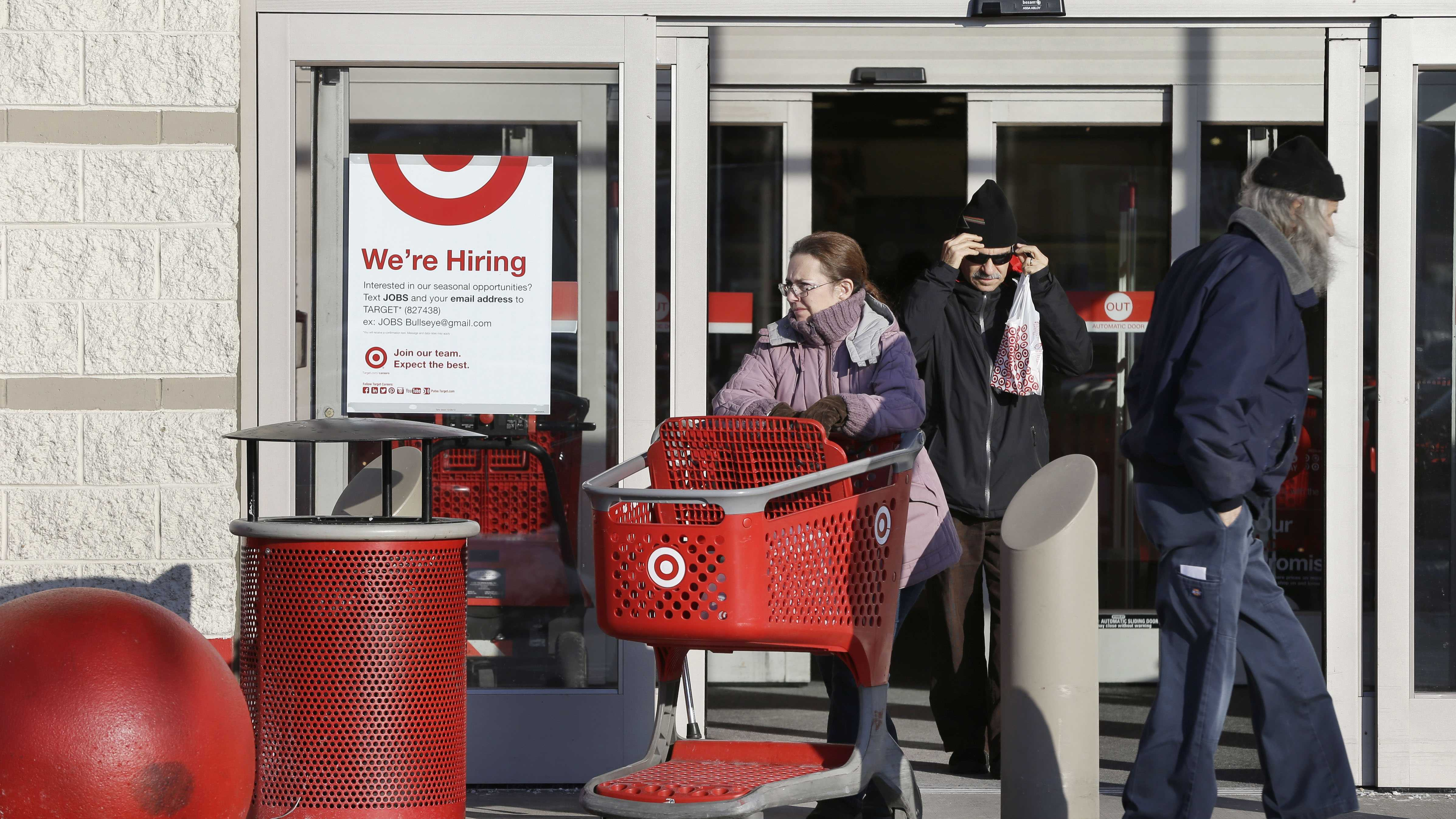 A woman pushes a shopping cart, center left, while departing a Target retail store Thursday, Dec. 19, 2013 in Watertown, Mass. Target says that about 40 million credit and debit card accounts may have been affected by a data breach that occurred just as the holiday shopping season shifted into high gear.