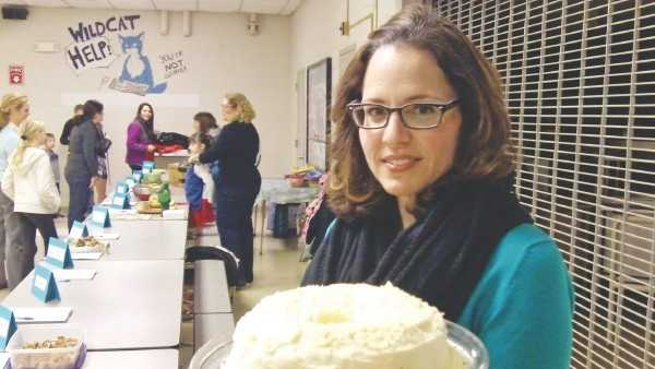 Wilmington High School teacher Brandi Torchia holds her red-velvet cake at the Wildcat Community Cookbook event Wednesday night at Wilmington High.