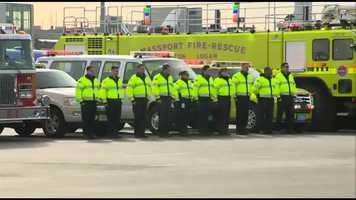 Massport workers stand in attention on the tarmac.