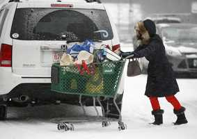 At Shaw's in Cohasset,with last years long power outages still in mind. residents stock up on essentials. Jackie Dionisio of Cohasset works to [push a shopping cart to her SUV.