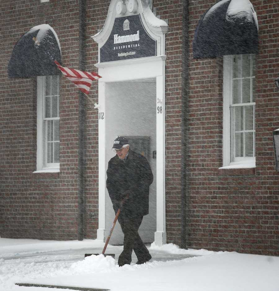 A man shovels snow from the front of a South Street business in Hingham.