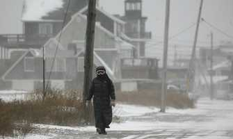 A woman with goggles walks along Turner Road in Scituate, high winds pushed sea spray hard, making it hard to see without eye protection.