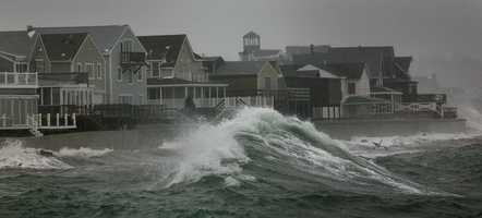 Waves pound the seawalls along the Sand Hills section of Scituate at high tide Thursday.