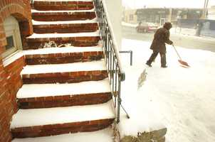 Joe Delia, of Hingham, owner of GiGi's Barber Shop in Chestnut Street in Quincy, clears in front of the shop. Blizzard conditions affected travel and pedestrians, as a winter storm hit Quincy, Thursday, Jan. 2, 2014.