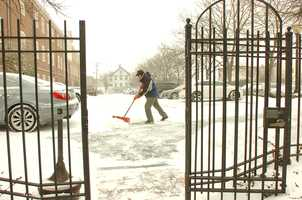 Willie Cullen, Facilities Manager at Quincy Mutual Fire Ins., clears walkways. Blizzard conditions affected travel and pedestrians, as a winter storm hit Quincy, Thursday, Jan. 2, 2014.
