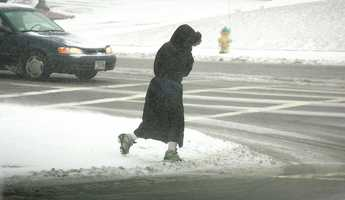 A pedestrian crosses McGrath Highway in Quincy. Blizzard conditions affected travel and pedestrians, as a winter storm hit Quincy, Thursday, Jan. 2, 2014.
