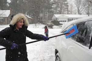 Taylor Decosta, 12, of West Bridgewater, helps clean off a car in her driveway in West Bridgewater during the snowstorm on Thursday, Jan. 2, 2014.