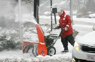 A man uses a snowplow along Elm St. in Braintree to clear the sidewalk, Thursday, Jan. 2, 2014.