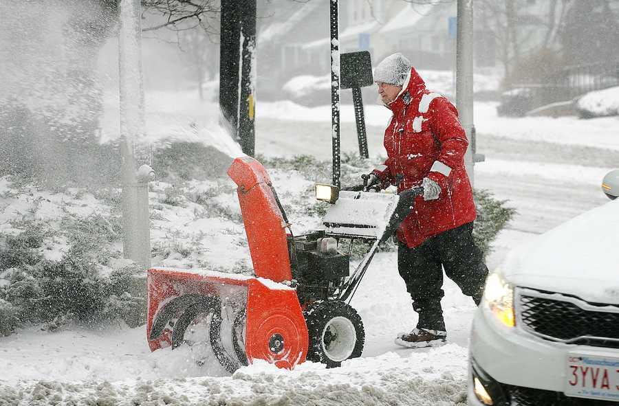 A man uses a snowplow along Elm St. in Braintree to clear the sidewalk, Thursday, Jan. 2, 2014.