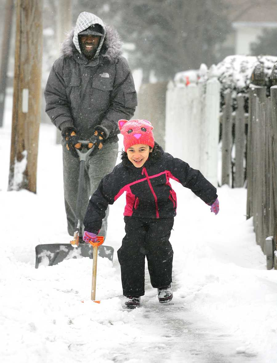 Olivia Singleton, 7, helps her dad, Kevin, clear snow from their Commercial Street home in Braintree, Thursday, Jan. 2, 2014. She had a snow day off from school both Thursday and Friday.
