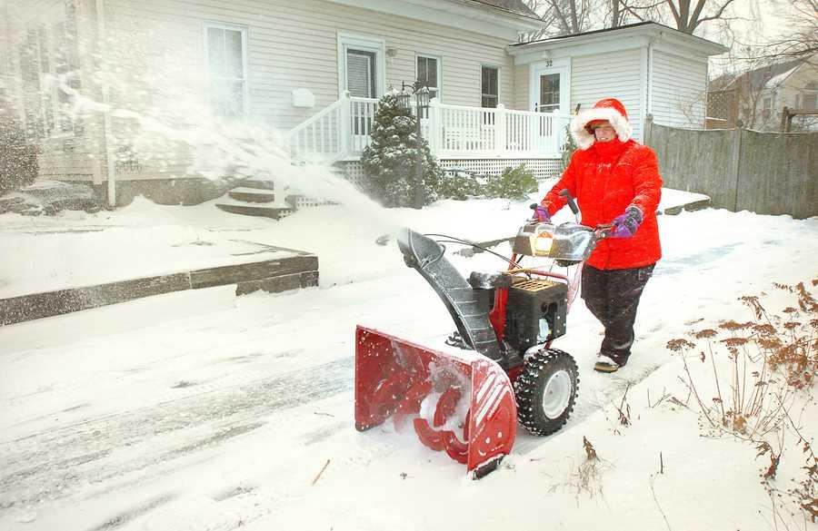 Lisa Julian, of Weymouth plows the driveway of her Lovell Street home, Thursday, Jan. 2, 2014.