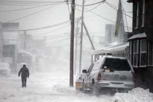 A man walks in the snow down a road along the shore in Scituate, Mass., Friday, Jan. 3, 2014. A winter storm slammed into the U.S. Northeast with howling winds and frigid cold, dumping nearly 2 feet (60 centimeters) of snow in some parts and whipping up blizzard-like conditions Friday.