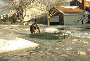 7th Ave resident Rick Bartley uses a boat to return his family to their home after the storm. Wife, Odile, son Will, 9 and daughter Alli,8, were aboard. They launched from 6th Ave since the flooded Scituate street was shallower than 7th Ave. They have lived in the home 12 years and seen a fair amount of flooding since.A major nor'easter included heavy snowfall and coastal flooding in Scituate, Friday, Jan. 3, 2014.