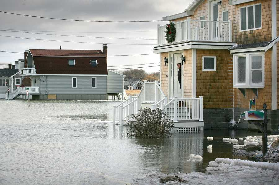 Kathy Condon looks out at a flooded Oceanside Drive. A major nor'easter included heavy snowfall and coastal flooding in Scituate, Friday, Jan. 3, 2014.