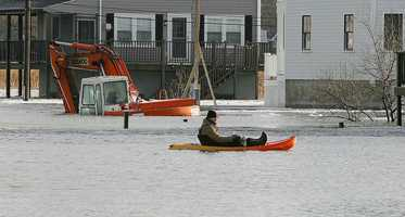 Sean Rielly, 18, a 6th Ave resident, kayaks to survey flooding near Oceanside Drive. A submerged piece of equipment is in the background. A major nor'easter included heavy snowfall and coastal flooding in Scituate, Friday, Jan. 3, 2014.Gary Higgins/The Patriot Ledger