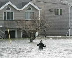 Jack Rielly, 9, wades through flood waters near his 6th Avenue home at Oceanside Drive. A major nor'easter included heavy snowfall and coastal flooding in Scituate, Friday, Jan. 3, 2014.