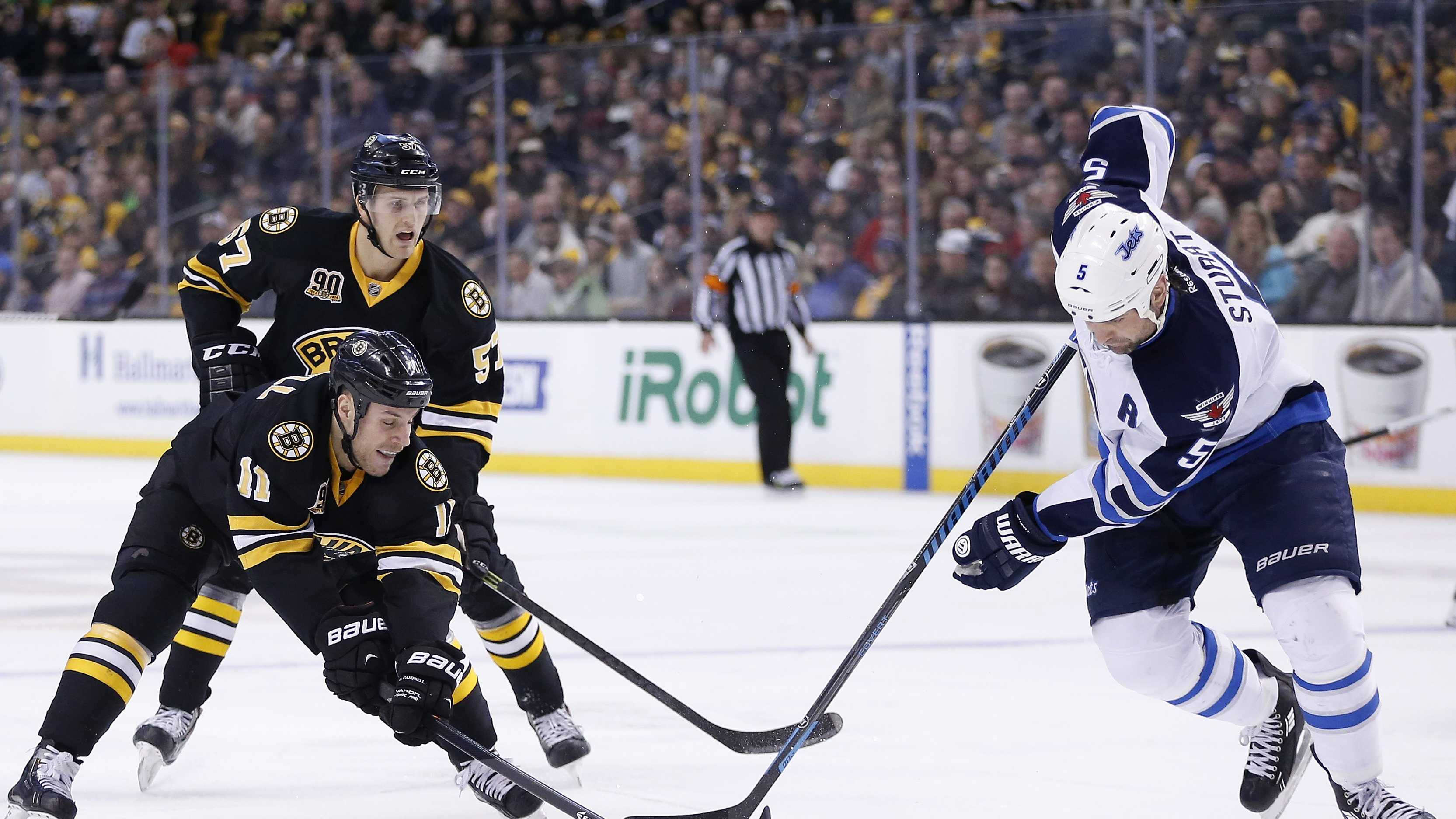 Boston Bruins' Gregory Campbell (11) and Winnipeg Jets' Mark Stuart (5) battle for the puck in the second period of an NHL hockey game in Boston, Saturday, Jan. 4, 2014.