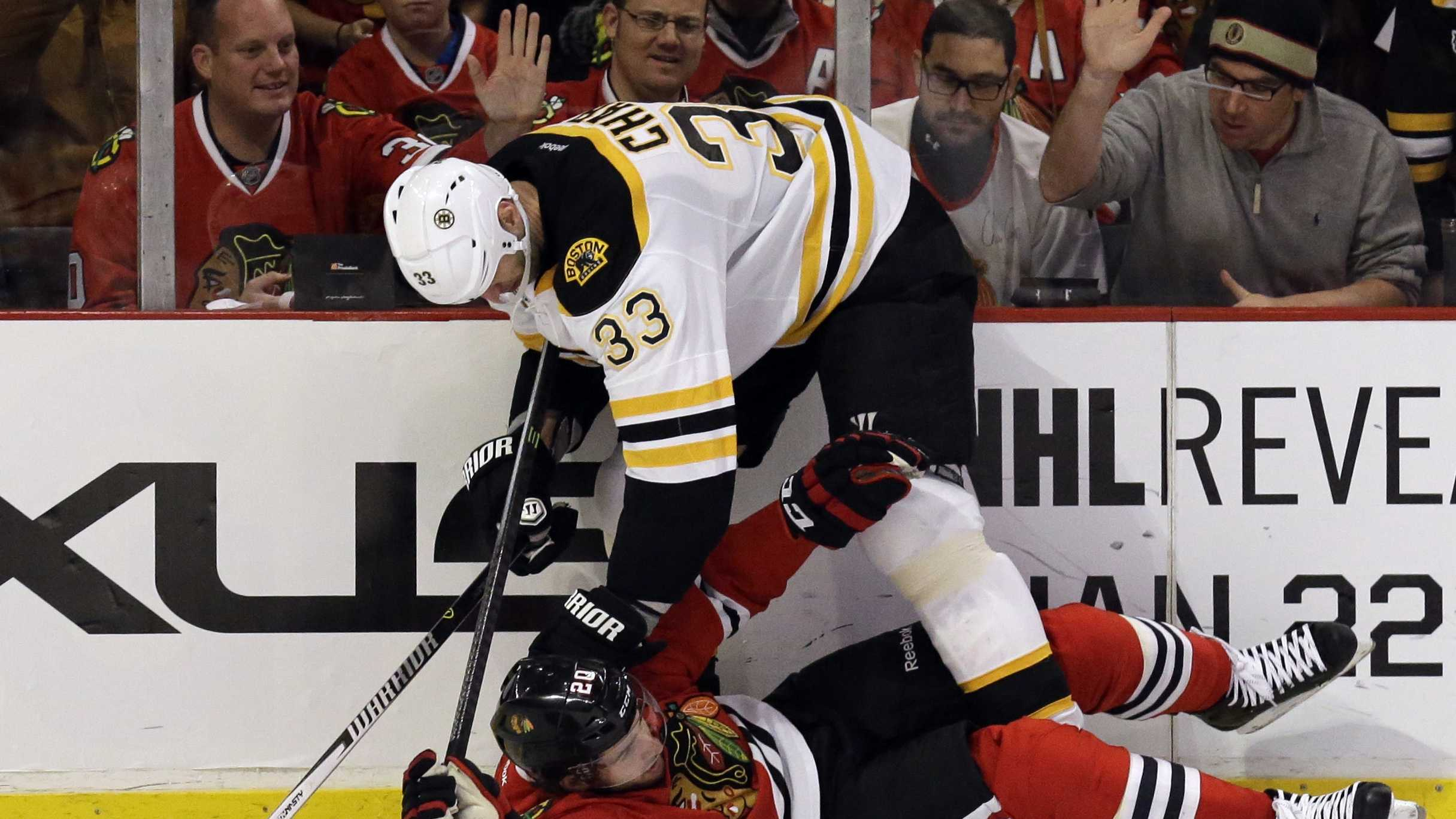 Chicago Blackhawks' Brandon Saad (20), bottom, is checked by Boston Bruins' Zdeno Chara (33) during the second period of an NHL hockey game in Chicago, Sunday, Jan. 19, 2014.