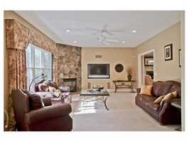 The breakfast area steps down to a warm & inviting family room w/ stone front gas fireplace