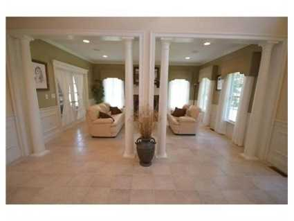 It has a huge foyer w/ columns that open to the living room w/gas fireplace.