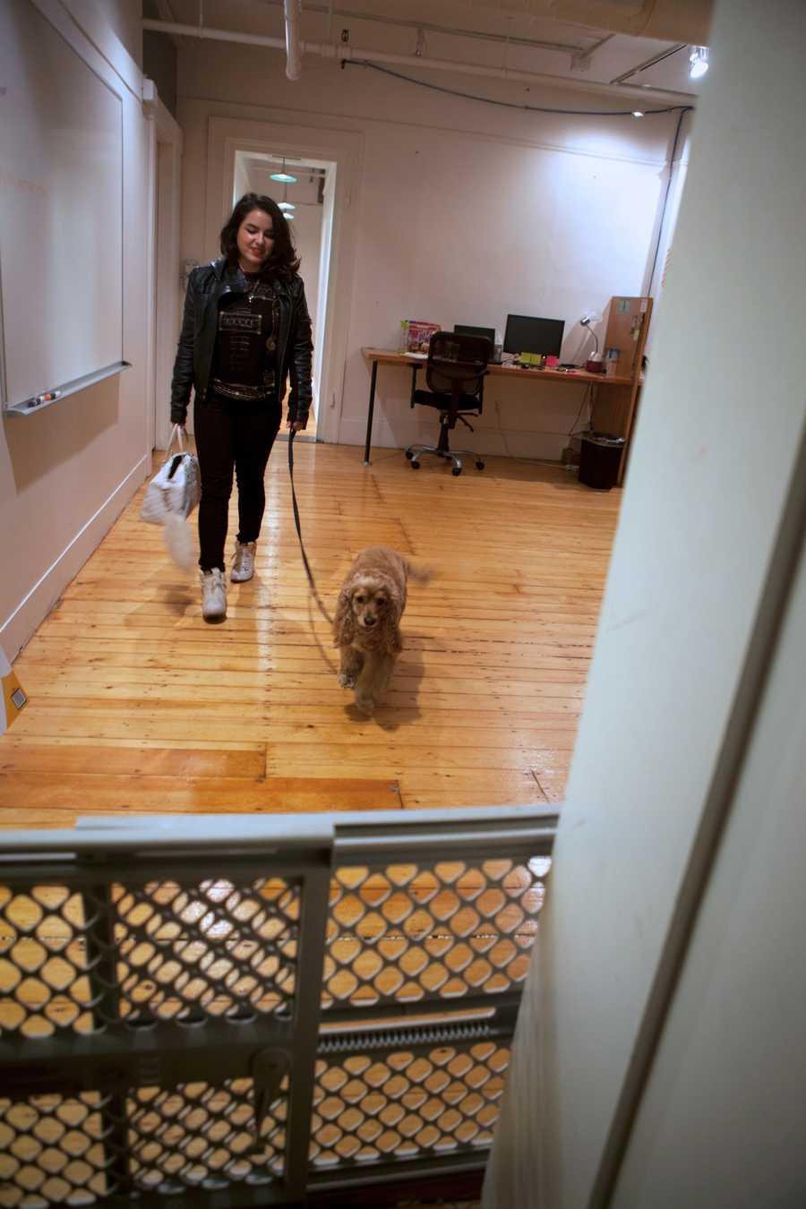 Molina walks out of her company with Charlie after work. Her company has fences at different doorways, to keep their dogs from running away.