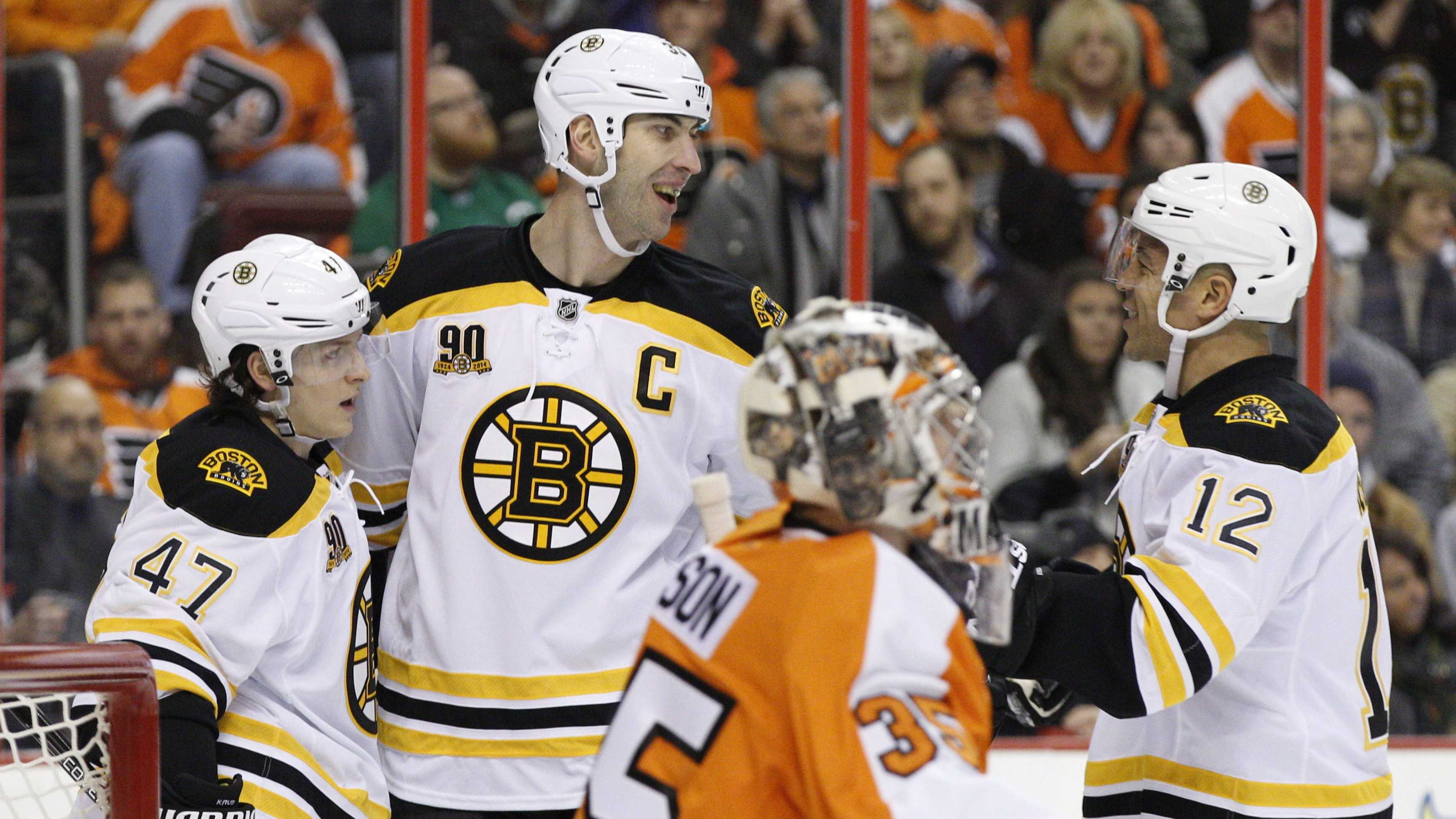 Boston Bruins' Zdeno Chara, top center, of Slovakia, celebrates his power play goal with Torey Krug, left, and Jarome Iginla, right, as Philadelphia Flyers' Steve Mason looks on during the first period of an NHL hockey game, Saturday, Jan. 25, 2014, in Philadelphia. (AP Photo/Chris Szagola)